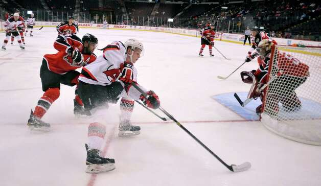 Ben Johnson of the Albany Devils tries to get around a Portland Pirates player at the Times Union Center on Sunday, Nov. 2, 2014, in Albany, N.Y.  (Paul Buckowski / Times Union) Photo: Paul Buckowski / 00029212C