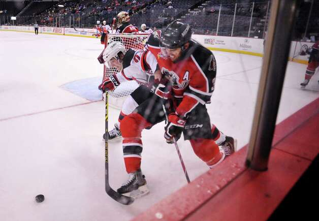 Graham Black, left, of the Albany Devils Brandon Gormley of the Portland Pirates battle for control of the puck at the Times Union Center on Sunday, Nov. 2, 2014, in Albany, N.Y.  (Paul Buckowski / Times Union) Photo: Paul Buckowski / 00029212C
