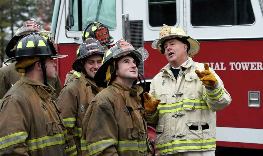 Troy Fire Department Battalion Chief Ed Cummings, right,  works with probationary firefighters during training Thursday morning Oct. 23, 2014 at the Colonie Fire Training Center in Colonie, N.Y.   (Skip Dickstein/Times Union) Photo: SKIP DICKSTEIN / 00029087A
