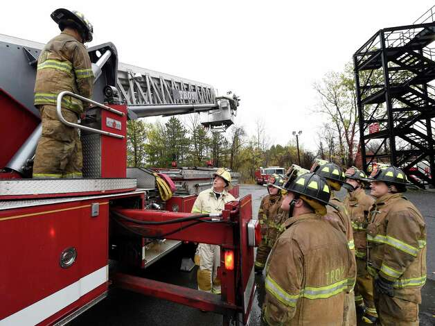 Troy Fire Department Battalion Chief Ed Cummings, center,  works with probationary firefighters during training Thursday morning Oct. 23, 2014 at the Colonie Fire Training Center in Colonie, N.Y.   (Skip Dickstein/Times Union) Photo: SKIP DICKSTEIN / 00029087A