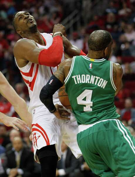 Rockets center Dwight Howard, taking a hit from the Celtics' Marcus Thornton, played 33 minutes Saturday night despite knee pain that leaves his status for Monday's game in Philadelphia up in the air. Photo: Karen Warren, Staff / © 2014 Houston Chronicle