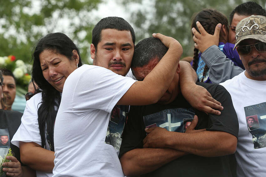 Pete Alvarado embraces his father, Pedro Alvardo, next to Pete's mother, Raquel Alvarado, during the burial for his siblings and their children, Erica Alvarado Rivera, 26, Alex Alvarado, 22, and Jose Angel Alvarado, 21, in El Control, Mexico on Sunday, November, 2, 2014. The siblings, U.S. Citizens from Progreso were found shot to death more than two weeks after they went missing from a restaurant near El Control.