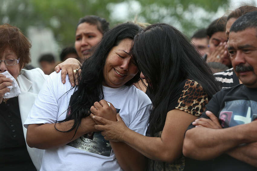 Raquel Alvarado is embraced during the burial for her children, Erica Alvarado Rivera, 26, Alex Alvarado, 22, and Jose Angel Alvarado, 21, with their father, Pedro Alvarado, right, at the cemetery in El Control, Mexico on Sunday, November, 2, 2014. The siblings, U.S. Citizens from Progreso, were found shot to death more than two weeks after they went missing from a restaurant near El Control.