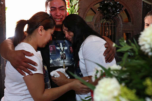 Juan Pablo Zapata holds Esmeralda Alvarado, left, and Raquel Alvarado, right, the mother of Erica Alvarado Rivera, 26, Alex Alvarado, 22, and Jose Angel Alvarado, 21, as they stand by the caskets for the siblings at the home of their father, Pedro Alvarado, before their funeral in El Control, Mexico on Sunday, November, 2, 2014. The siblings, U.S. Citizens from Progreso, were found shot to death more than two weeks after they went missing from a restaurant near El Control. Photo: Lisa Krantz / SAN ANTONIO EXPRESS-NEWS