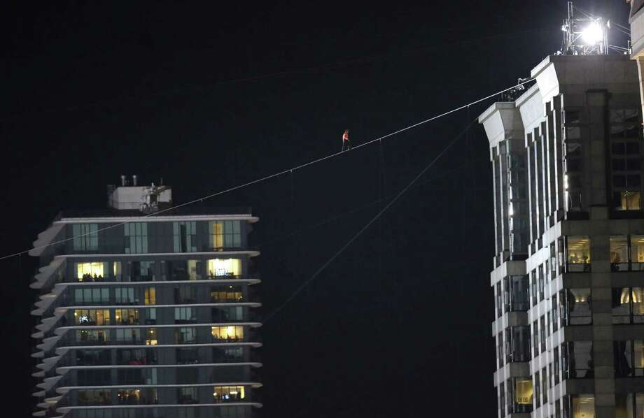 Nik Wallenda makes his first tightrope walk Sunday across the Chicago River between two skyscrapers. Photo: Charles Rex Arbogast, STF / AP