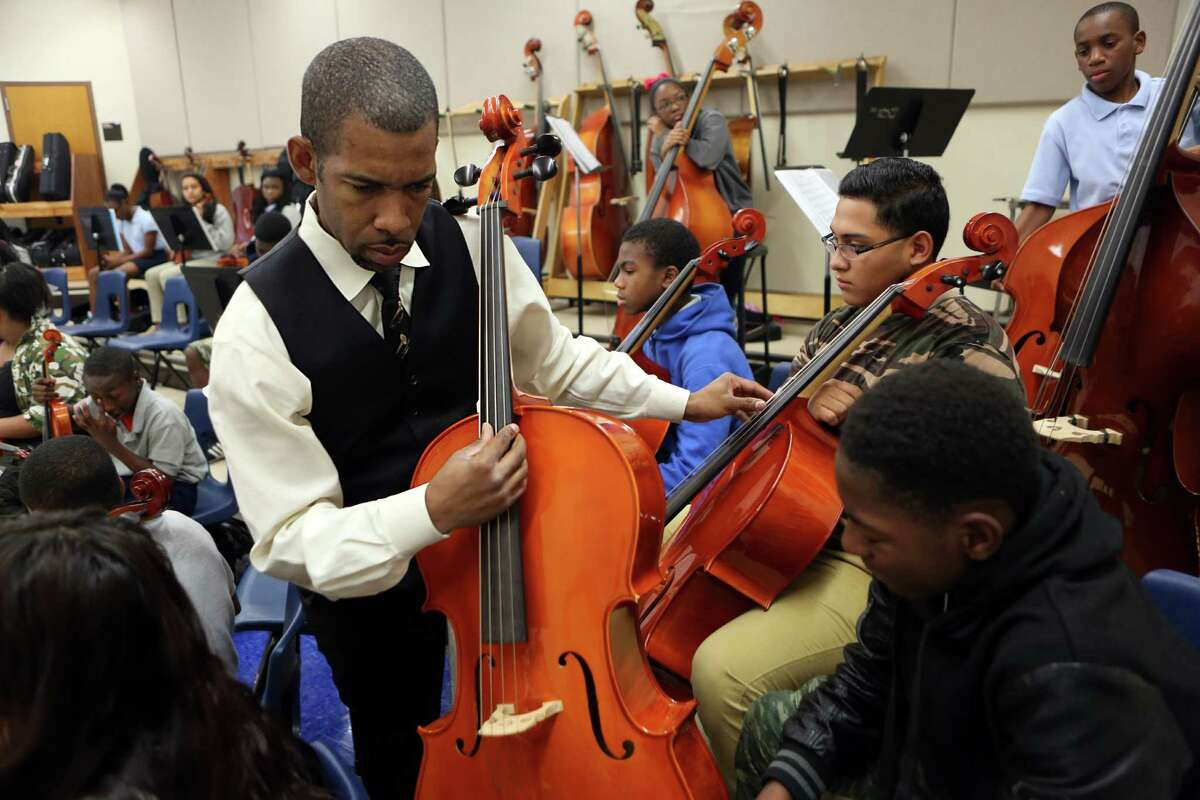 David White helps tune cellos during Orchestra class at Williams Middle School in Acres Home on Friday, Oct. 31.