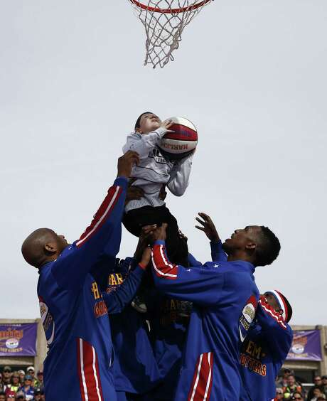 Rodney Memmel, 8, gets a lift from Harlem Globetrotters during a basketball demonstration before the NASCAR Sprint Cup Series auto race at Texas Motor Speedway in Fort Worth on Sunday. Photo: Jim Cowsert, FRE / FR170531 AP