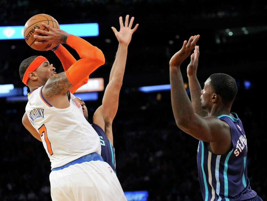 Carmelo Anthony, shooting over the Hornets' Lance Stephenson, is the 40th player with 20,000 points. Photo: Bill Kostroun, FRE / FR51951 AP
