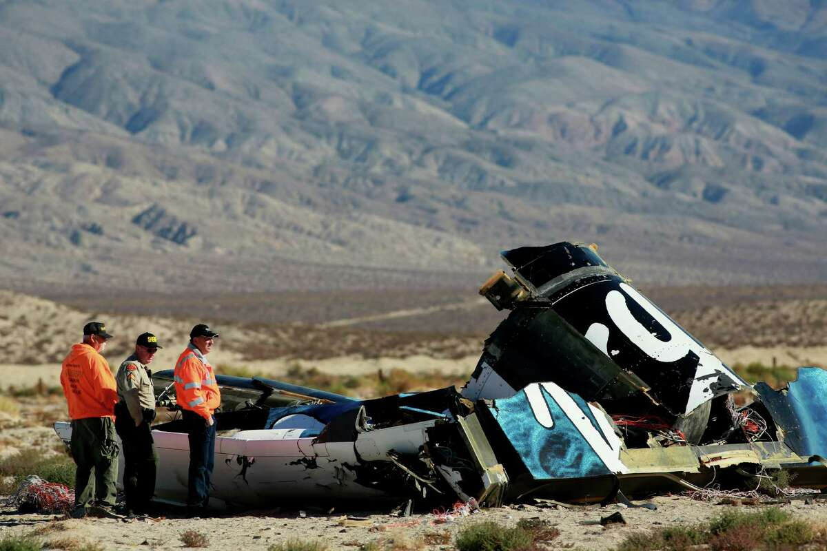 MOJAVE, CA - NOVEMBER 2 : Sheriff's deputies inspect the wreckage of the Virgin Galactic SpaceShip 2 in a desert field November 2, 2014 north of Mojave, California on The Virgin Galactic SpaceShip 2 crashed on October 31, 2014 during a test flight, killing one pilot and seriously injuring another. (Photo by Sandy Huffaker/Getty Images) *** BESTPIX ***