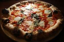 "Flour + Water (2401 Harrison St, San Francisco)  Here's what Michael Bauer wrote in his initial review: ""[The pizza] sets standards for wood-oven Neapolitan style in the Bay Area ... The crust could easily have been used in a training manual for the Associazione Verace Pizza Napoletana. It's airy and breadlike at the charred rim with a touch of chewiness and a hint of crispness."""