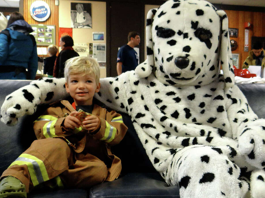 Grayson Ahern, 2, of Westport with Sparky the firefighting mascot at Southport Volunteer Fire Department's open house Saturday morning. Photo: Mike Lauterborn / Fairfield Citizen