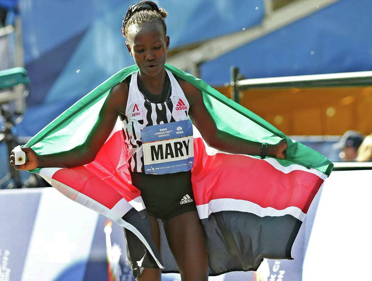 Women's winner Mary Keitany of Kenya walks beyond the finish line wearing her country's flag after coming in first in the 44th annual New York City Marathon in New York, Sunday, Nov. 2, 2014. (AP Photo/Kathy Willens) ORG XMIT: NYKW118