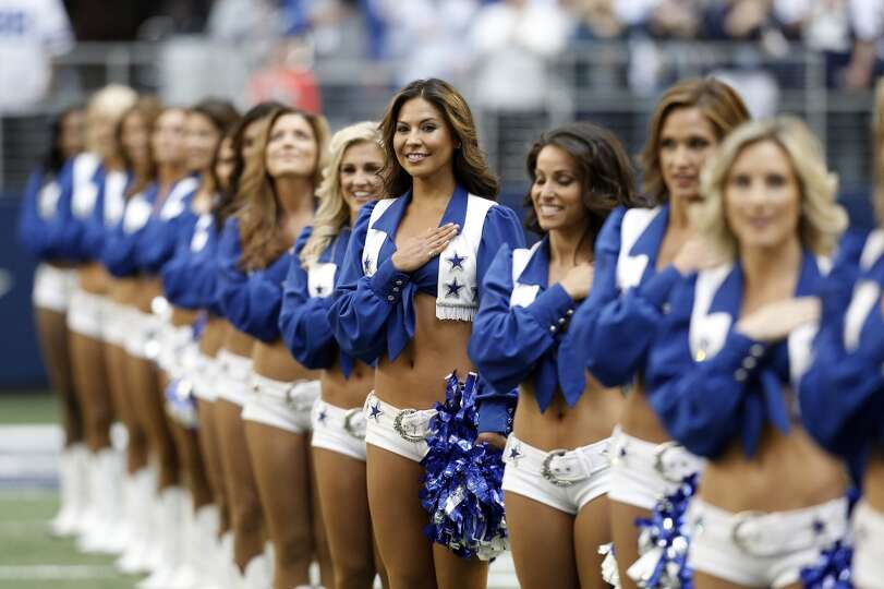 Dallas Cowboys cheerleaders hold their hands over their hearts during the playing of the National An