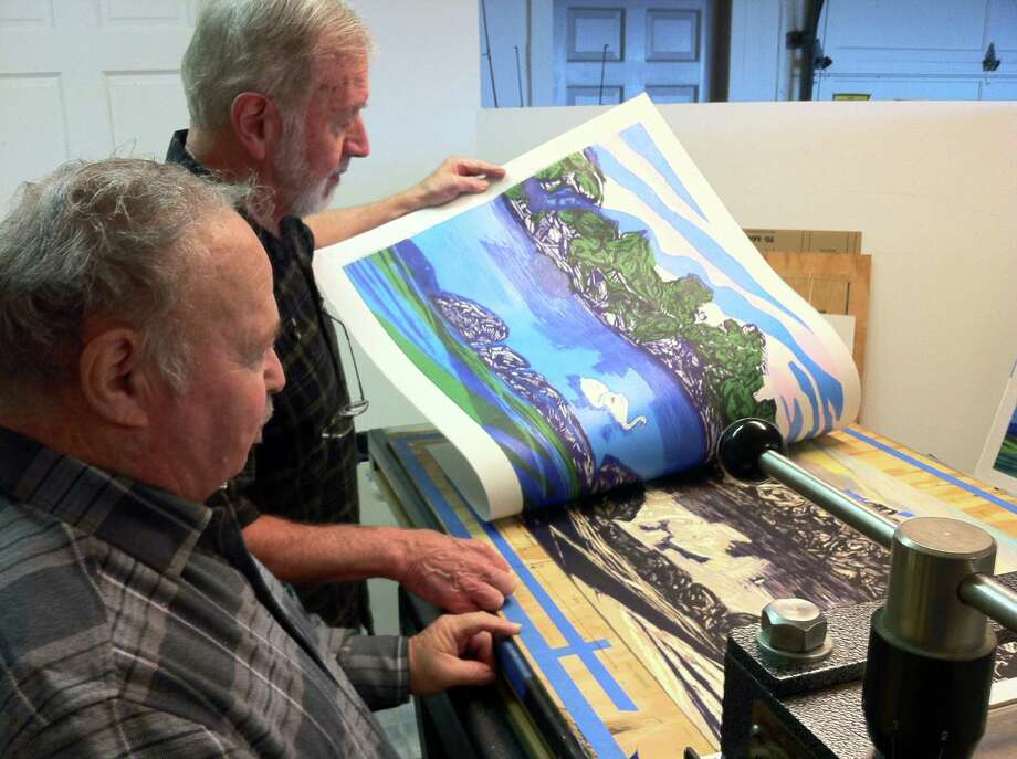 Stamford, Conn., artist Donald Axleroad looks over a print inspired by Greenwich, Conn.'s Byram Park, in his home studio on Oct. 30, 2014. It is part of a special edition run for his new retrospective show at the Greenwich Arts Council's Bendheim Gallery. It will run through Dec. 12, 2014. He is assisted by Charles Wiesehahn, an area photographer who helps Axleroad with his work. Photo: Contributed Photo / Stamford Advocate Staff photo