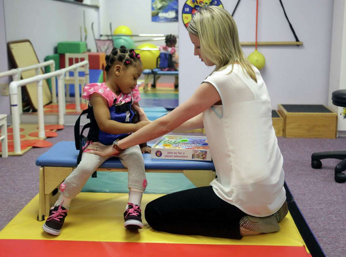 Certified occupational therapy assistant Minnie Baker works with patient Latiya Hadnot in the pediatric physical therapy gym at Cole Pediatric Therapy in Conroe.