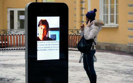 FILE- In this file photo dated Thursday, Jan. 10, 2013, a woman stands next to a screen showing a portrait of Steve Jobs on the recently erected memorial to late Apple Corp. co-founder in the courtyard of the Techno Park of the St. Petersburg National Research University of Information Technologies, Mechanics and Optics (ITMO University) in St. Petersburg, Russia. The six-foot tall interactive iPhone shaped memorial has been taken down in response to last week's announcement that CEO of Apple, Tim Cook is openly gay. (AP Photo/Dmitry Lovetsky, FILE )