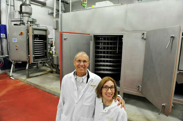 Steve Schonwetter, left, CEO, and his daughter, Stacie Waters, president at the Bilinski Sausage Manufacturing Company, pose for a photo in a new manufacturing area on Monday, Nov. 3, 2014, in Cohoes, N.Y.  This manufacturing area has a spiral oven and spiral chiller that allows for continuous operation of the making, cooking and chilling or freezing of meat products without human hands having to touch the product.  The company is expanding their product line to include meatballs and breakfast patties, which will be made with the spiral oven and chiller. The firm will add 10 to 20 jobs to its 50-person workforce to meet the expanded production. (Paul Buckowski / Times Union) Photo: Paul Buckowski / 00029331A