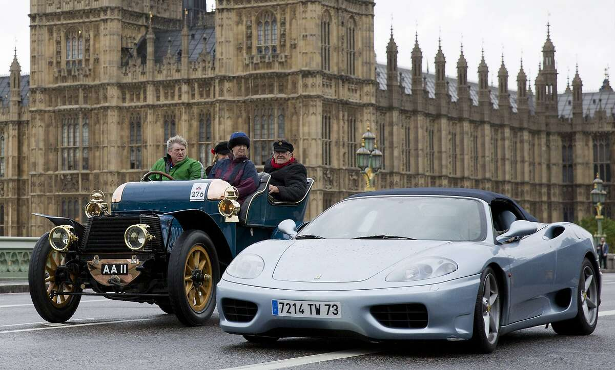 Blasted newfangled machines! Doug Hill and his passengers in their 1903 Daimler tonneau look across at a Ferrari overtaking them on Westminster Bridge in front of the Houses of Parliament in London  as they take part in the London to Brighton Veteran Car Run, which has been held since 1896. Gerneally, only cars built before 1905 are eligible. Hundreds of participants drive from London to Brighton at an average speed of around 20 mph.