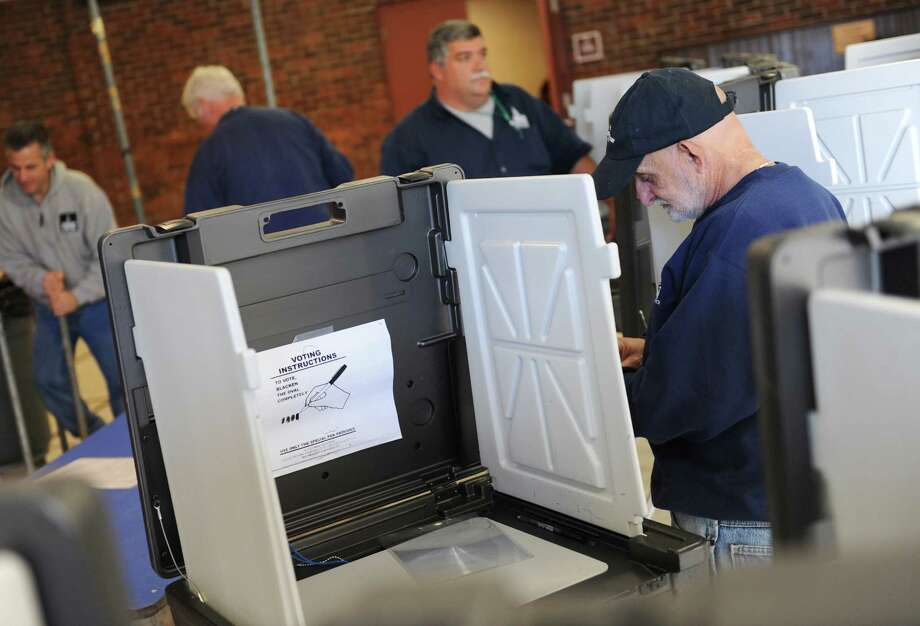Sam Barresi, right, and other Building Construction & Maintenance workers set up voting booths at Greenwich High School in Greenwich, Conn. Monday, Nov. 3, 2014.  12 polling stations for District 7 and 7A were set up at the high school for Tuesday's election. Photo: Tyler Sizemore / Greenwich Time