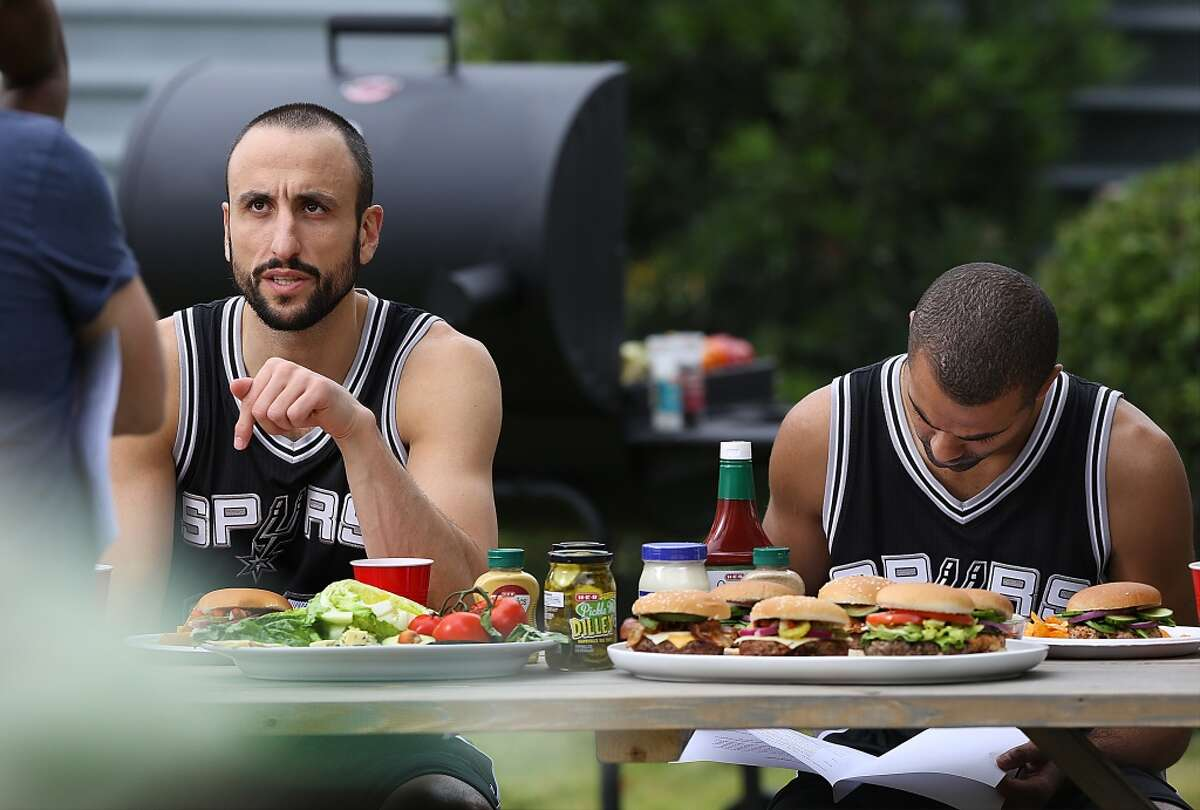 San Antonio Spurs Manu Ginobili, left, and Tony Parker take their places during production of new HEB commercials being filmed outside the NBA Champion's practice facility. Monday, Nov. 3, 2014.