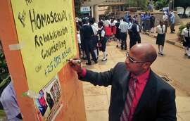 "Ugandan anti-gay activist Pastor Martin Ssempa posts up a public notice offering ""rehabilitation"" for homosexuals at Uganda's National Theatre in Kampala, Uganda. Will Apple CEO Tim Cook's announcement that he is gay change perceptions of homosexuality in countries where gay sex is illegal?"