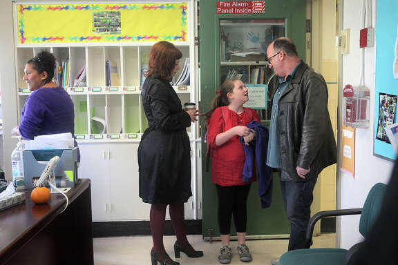 Paraprofessional Sandra Navarro (left) passes by as student Ivy Dubiner (center) stands with her mom, Carrie Swing, and dad, David Dubiner, in the office of Harvey Milk Civil Rights Academy in San Francisco on Nov. 3, 2014.