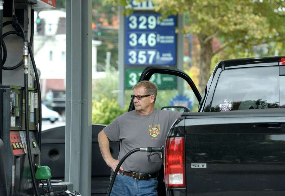 Bud Koral, of New Fairfield, pumps gas into his truck at the Friendly Service Station, on Main Street, in Danbury, Conn, on Wednesday, October 15, 2014. With gas prices in Connecticut the lowest they have been since 2011 analysts are predicting we could see gasoline below $3.00 a gallon. Photo: H John Voorhees III / The News-Times Staff Photographer
