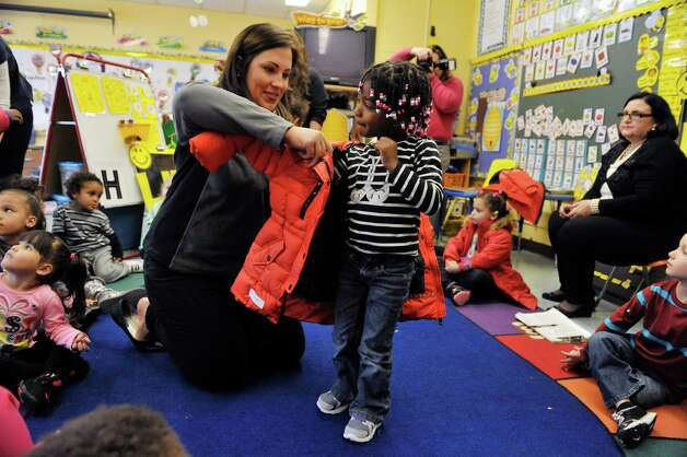 Amanda Goyer, left, foundation and public relations administrator with Cap Com, helps Aziya Rowlett put on her new coat at Troy School 12 on Monday, Nov. 3, 2014, in Troy, N.Y. Cap Com is donating the new coats for pre-K students at Troy public schools 2 and 12.  The Commission on Economic Opportunity organized the event.  The coats were purchased through B. Lodge & Co., which works with vendors to get the coats at close to cost.  (Paul Buckowski / Times Union) Photo: Paul Buckowski / 00029312A