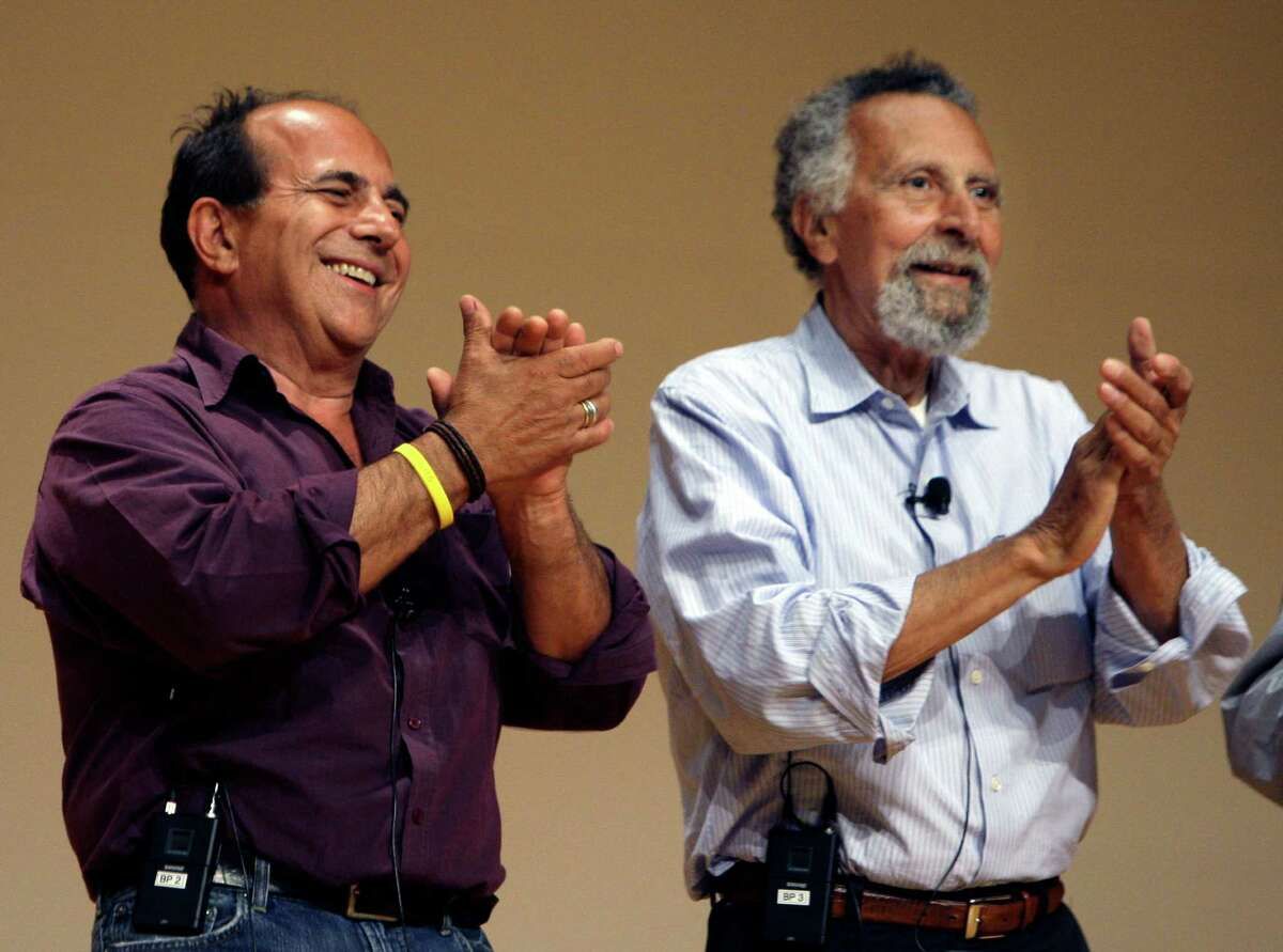 """In this June 19, 2008 photo, brothers Ray, left, and Tom Magliozzi, co-hosts of National Public Radio's """"Car Talk"""" show, applaud during a premier of a cartoon show about them in Cambridge, Mass. NPR says Tom Magliozzi died Monday, Nov. 3, 2014 of complications from Alzheimer's disease. He was 77. (AP Photo/Charles Krupa)"""