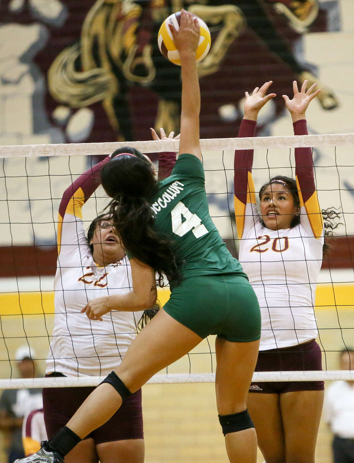 Harlandale's Valeria Stokes, right, and Lizette Pedroza try to block a shot by McCollum's Neyda Sanchez during their match at Harlandale on Oct. 28. McCollum beat Harlandale in four sets, wrapping up the District 28-5A with a perfect 16-0 slate.