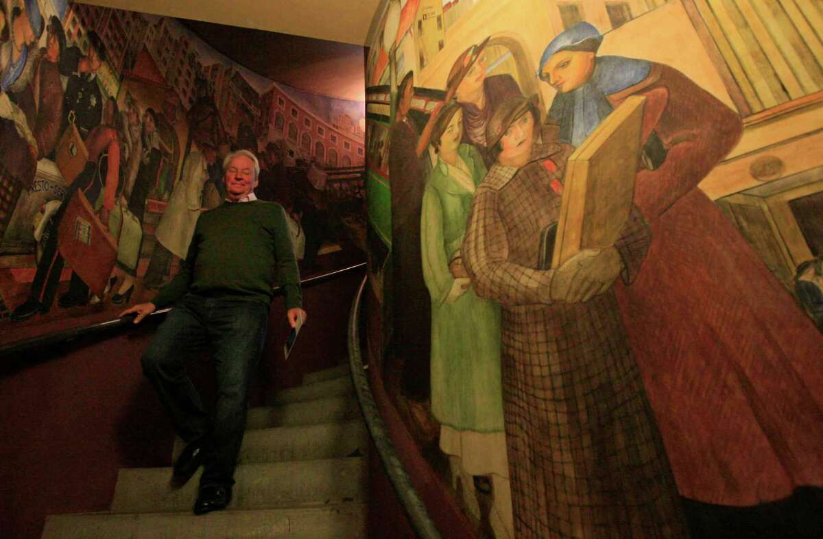 Davy Crockett, tour director for Coit Tower, walks past the newly restored mural