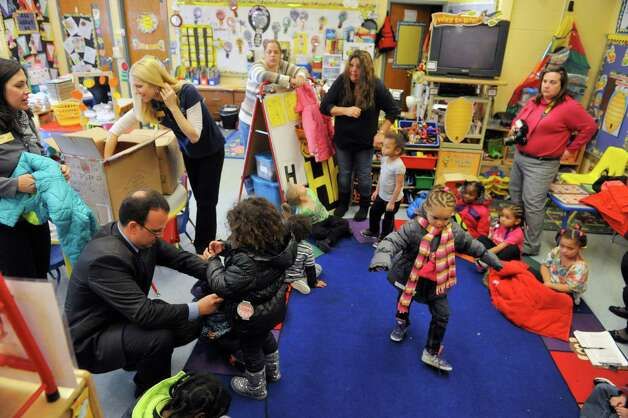 Mark Yonally, bottom left, president of B. Lodge and Co. helps a child put on her new coat at Troy School 12 on Monday, Nov. 3, 2014, in Troy, N.Y.  Yonally along with employees of Cap Com came to the school to hand out coats to the children.  Cap Com is donating the new coats for pre-K students at Troy public schools 2 and 12.  The Commission on Economic Opportunity organized the event.  The coats were purchased through B. Lodge & Co., which works with vendors to get the coats at close to cost.  (Paul Buckowski / Times Union) Photo: Paul Buckowski / 00029312A