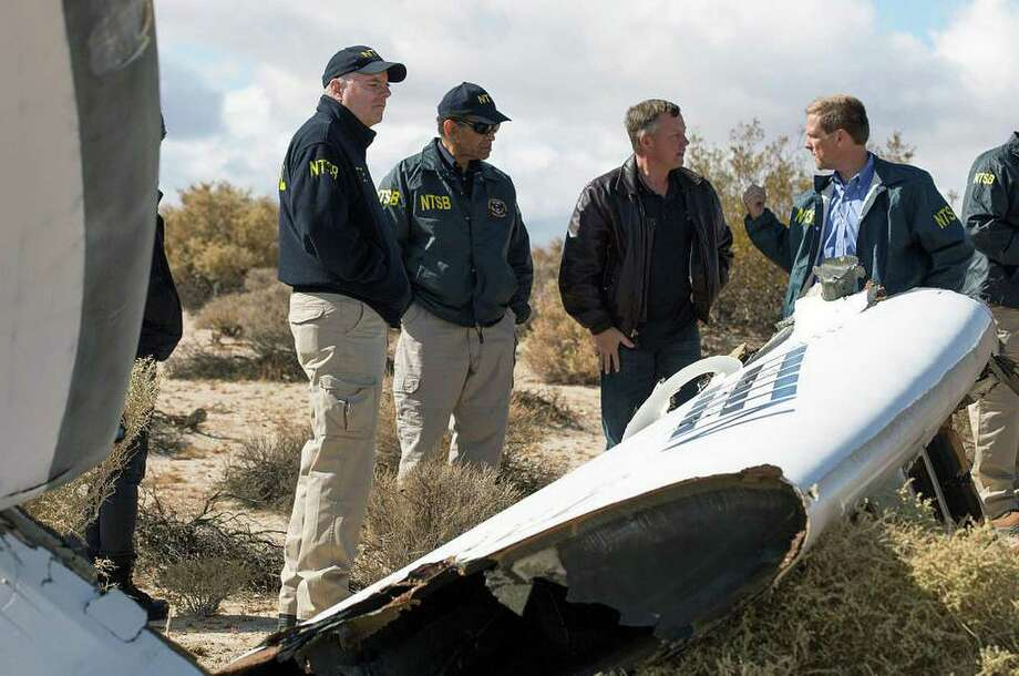 """In this Nov. 1, 2014, photo provided by the National Transportation Safety Board, Virgin Galactic pilot Todd Ericson, right, talks with NTSB Acting Chairman Christopher A. Hart, second from left, at the SpaceShipTwo accident site with investigators in Mojave, Calif. The cause of Friday's crash of Virgin Galactic's SpaceShipTwo has not been determined, but investigators found the """"feathering"""" system, which rotates the tail to create drag, was activated before the craft reached the appropriate speed, National Transportation Safety Board Acting Chairman Christopher Hart said. (AP Photo/NTSB) Photo: HOPD / NTSB"""