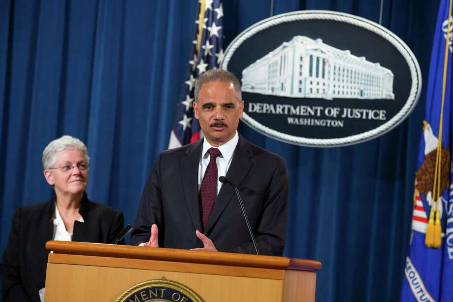 Environmental Protection Agency Administrator Gina McCarthy listens at left as Attorney General Eric Holder speaks during a news conference at the Justice Department in Washington, Monday, Nov. 3, 2014. The Justice Department and EPA announced that Hyundai Motor Company and Kia Motors Company would pay a $100 million penalty for overstating vehicle fuel standards. (AP Photo/Evan Vucci) Photo: Evan Vucci, STF / AP