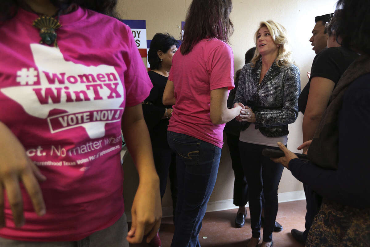 Democrat Wendy Davis meets with supporters and campaign workers at a West Side field office. On her last day of campaigning before today's election, she attacked rival Greg Abbott's conservative record.