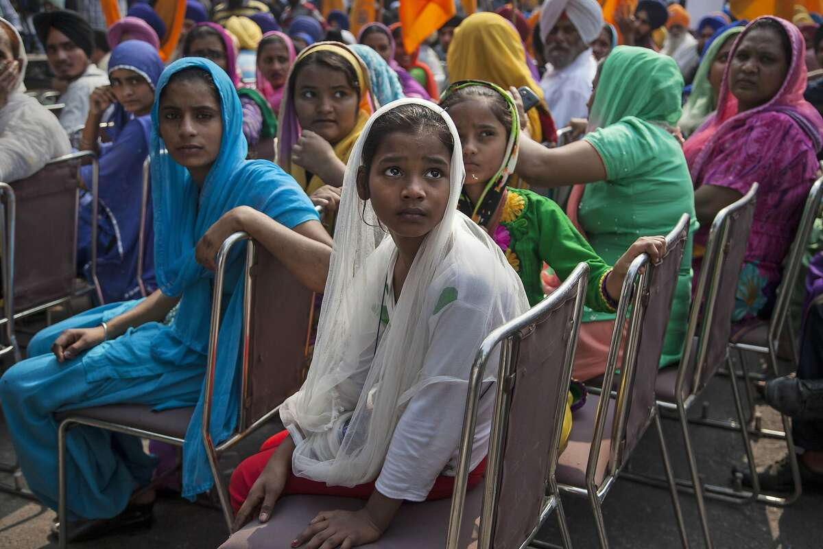 Indian Sikh girls watch others shout slogans during a protest demanding justice for victims of the 1984 anti-Sikh riots in New Delhi, India, Monday, Nov. 3, 2014. More than 3000 Sikhs were killed in the riots that followed the assassination of former Prime Minister Indira Gandhi by her Sikh bodyguards on October.31,1984. The protestors were also holding placards expressing solidarity with the Kashmiris, people of India's northeast and the Tamils in Sri Lanka who are fighting for their rights. (AP Photo/Tsering Topgyal)