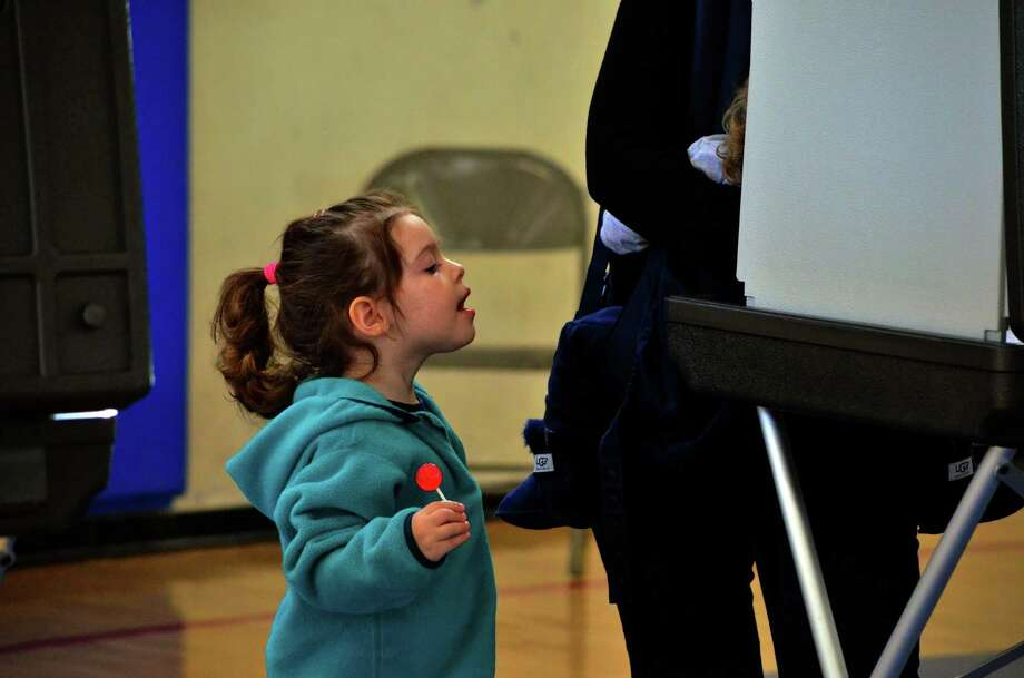A child looks on as her mother votes in Town Hall on Nov. 4. Photo: Megan Spicer / Darien News