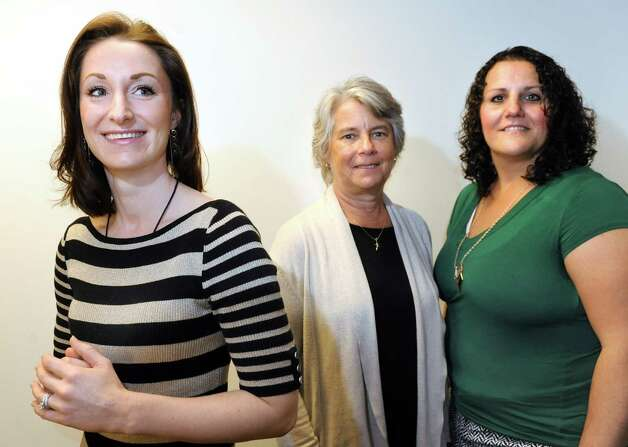 Physician's assistant Lindsay Schweikarth, left, joins Sarah Hafensteiner of Coeymans, center, and Rebecca Burch of Troy, both who have had breast reconstruction surgery, on Wednesday, Oct. 15, 2014, at Albany Medical Center in Albany, N.Y. Schweikarth is the resident expert in tattooing realistic-looking nipples on reconstructed breasts. (Cindy Schultz / Times Union) Photo: Cindy Schultz / 10028933A