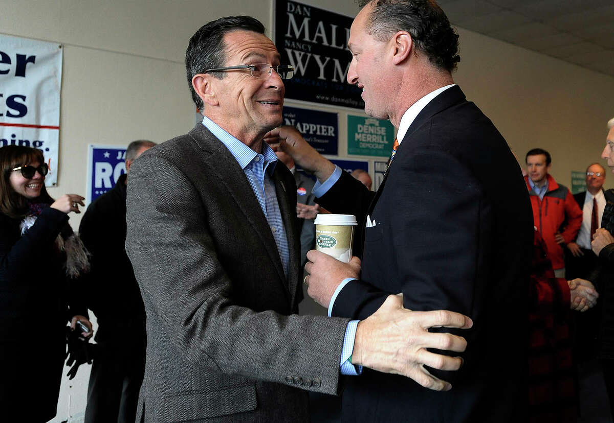Connecticut Gov. Dannel P. Malloy speaks to Manchester, Conn. Mayor Jay Moran at Manchester Democratic headquarters, Tuesday, Nov. 4, 2014, in Manchester, Conn. Malloy is facing Republican candidate Tom Foley in today's election. (AP Photo/Jessica Hill)