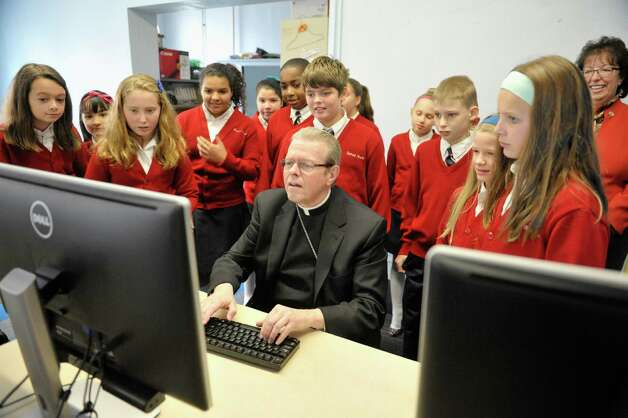 Surrounded by Sacred Heart School students, Bishop Edward Scharfenberger composes his first tweet as he launched his Twitter account @AlbBishopEd in the school's computer room on Tuesday, Nov. 4, 2014, in Troy, N.Y.  The Bishop also celebrated Mass at Sacred Heart church.   (Paul Buckowski / Times Union) Photo: Paul Buckowski / 00029256A