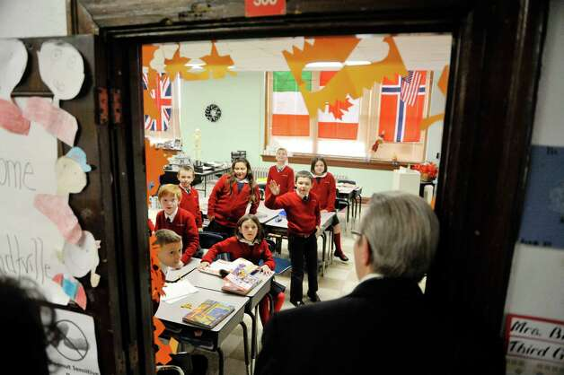 Bishop Edward Scharfenberger pokes his head into a classroom at Sacred Heart School to say hello to the students on Tuesday, Nov. 4, 2014, in Troy, N.Y.  The Bishop toured the school after celebrating Mass at Sacred Heart Church.  (Paul Buckowski / Times Union) Photo: Paul Buckowski / 00029256A