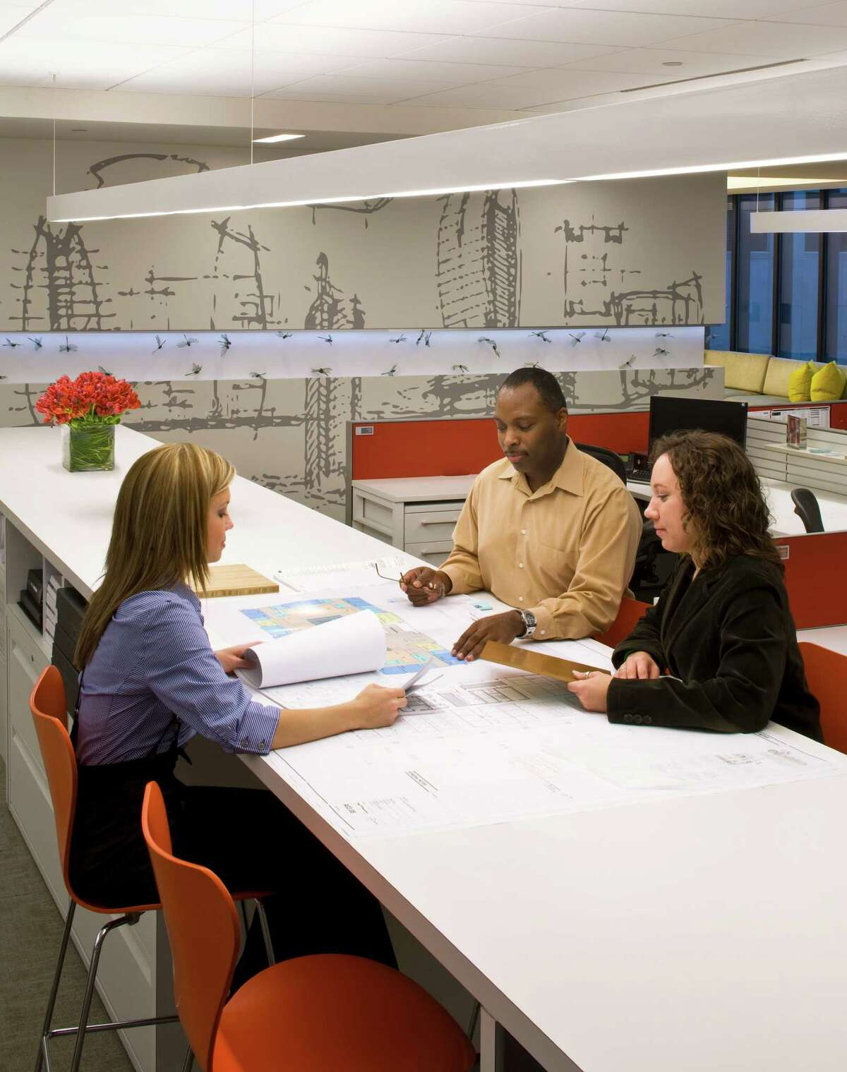 Employees review architectural plans in Gensler's Houston office. The firm was named as one of Houston's Top Workplaces.