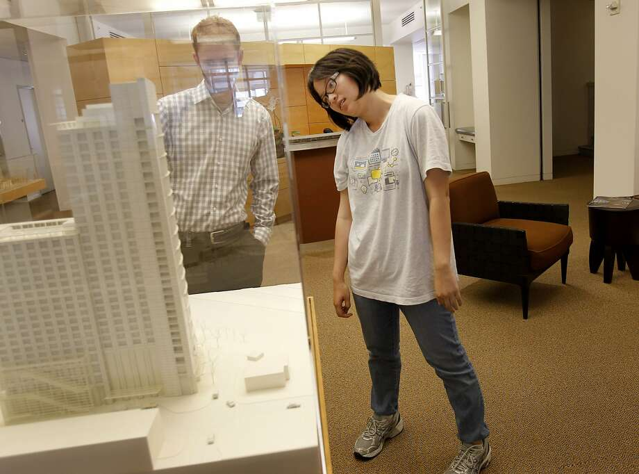 Former intern and now junior architect Justin Marks (left) shows current intern Nicole Chin some of the projects in the past from Hornbergher and Worstell. Photo: Brant Ward, The Chronicle