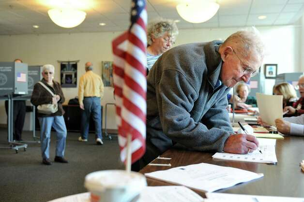 Jim Gibney Jr., right, signs in to vote on Election Day on Tuesday, Nov. 4, 2014, at the Jewish Community Center in Niskayuna, N.Y. (Cindy Schultz / Times Union) Photo: Cindy Schultz / 00029313A