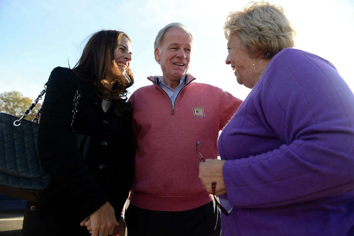 Republican gubernatorial challenger Tom Foley and his wife Leslie talk to deputy Registrar of Voters Jill Karpovich while campaigning Tuesday, Nov. 4, 2014 outside Quaker Farms School in Oxford, Conn.