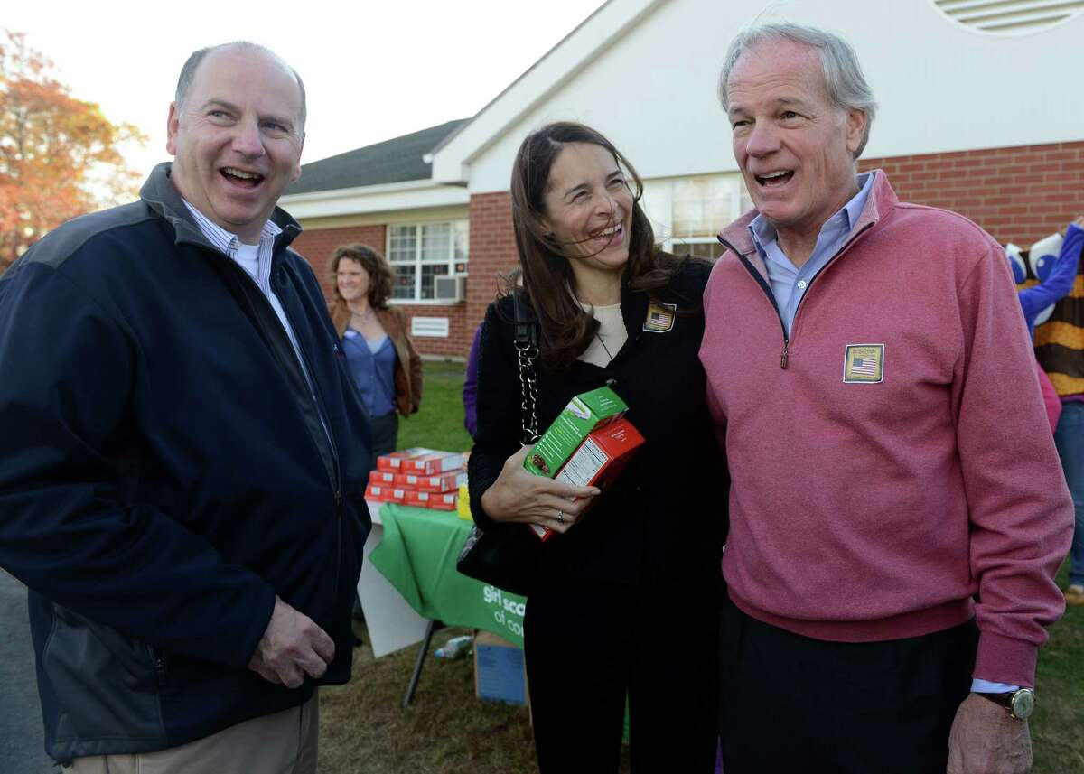 Republican gubernatorial challenger Tom Foley and his wife Leslie talk with state Rep. David Labriola while campaigning Tuesday, Nov. 4, 2014 outside Quaker Farms School in Oxford, Conn.