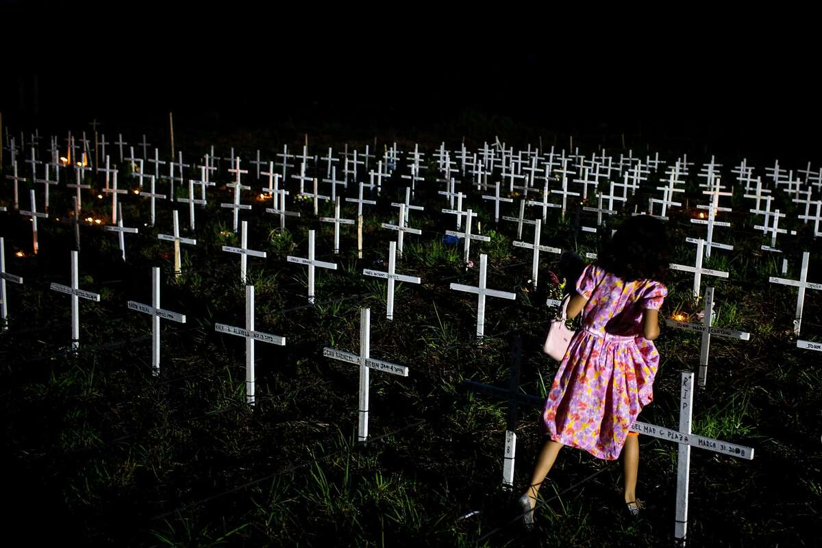 CROSSES FOR VICTIMS OF HAIYAN: A young Filipina tries to find the marker of a loved one at a newly constructed mass grave for 3,000 Typhoon Haiyan victims on the grounds of the Holy Cross Cemetery in Tacloban, Leyte.