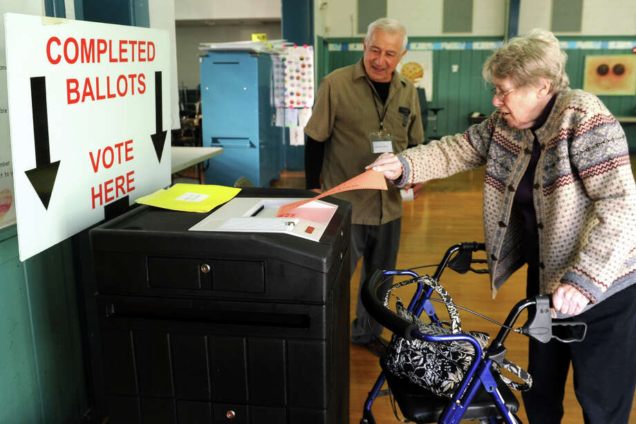 Sally Redston submits her ballots on Election Day at Chapel Street School, in Stratford, Conn. Nov. 4, 2014. Redston is seen her with pole attendant Nick Vitino. Photo: Ned Gerard / Connecticut Post