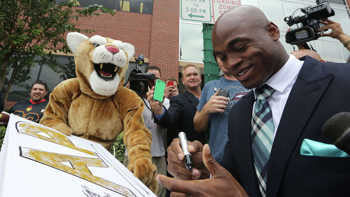 Minnesota Vikings star running back Adrian Peterson signs an autograph for a man dressed as a wild cat with a sign supporting Peterson at the Montgomery County courthouse in Conroe, TX Tuesday November 4, 2014. Peterson avoided jail time in a plea agreement reached with prosecutors to resolve his child abuse charge. Peterson's plea to the Class A misdemeanor comes with two years of deferred adjudication. Peterson also received a $4,000 fine and 80 hours of required community service. /