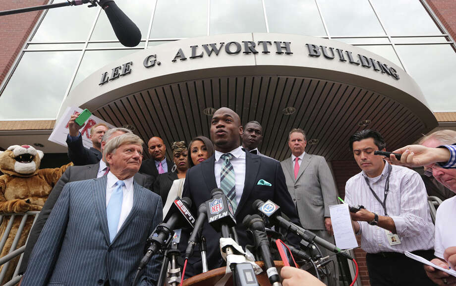 (center) Minnesota Vikings star running back Adrian Peterson speaks with the media before departing from the Montgomery County courthouse in Conroe, TX Tuesday November 4, 2014. Peterson avoided jail time in a plea agreement reached with prosecutors to resolve a child abuse case involving Peterson's 4-year-old son. Photo: Billy Smith II, Billy Smith II | Houston Chronicle / © 2014 Houston Chronicle